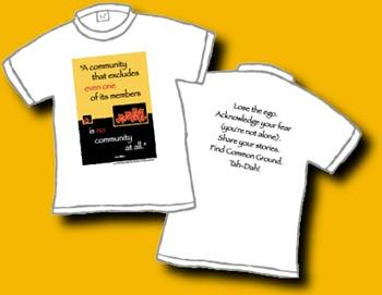"This is a 100% cotton white shirt. On the front is a large box – the top 2/3 school bus yellow, and the bottom black. There a red hearts scattered and words saying: ""A community that excludes even one of its members is no community at all."" On the back in black letters it says: Lose the ego. Acknowledge your fear (you're not alone). Share your Stories. Find Common Ground. Tah – Dah!  This is an original Dan Wilkin's design."